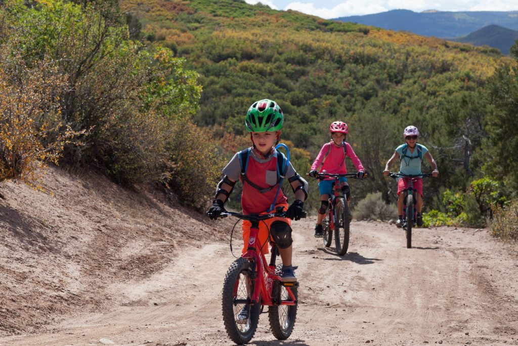 a young boy leads his mom and sister up the climb on a dirt road in Aspen, CO