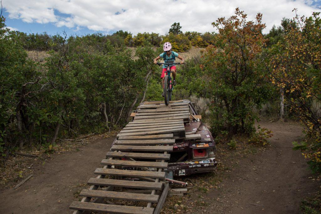 woman in a pink bike helmet mountain biking down a ramp in Carbondale, CO