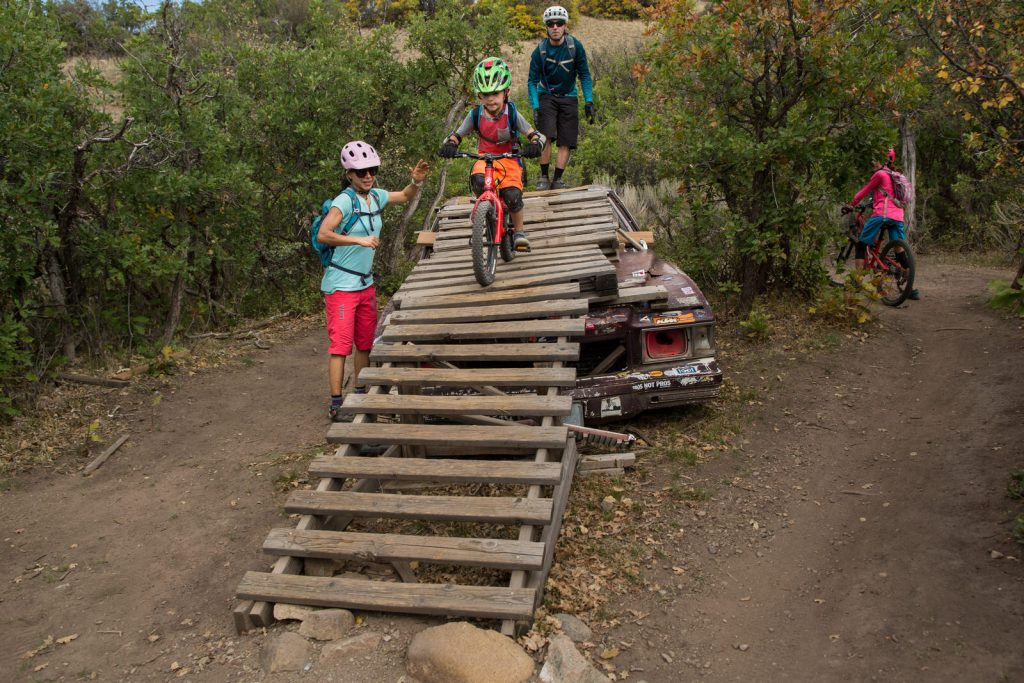 young boy riding a mountain bike down a ramp in Carbondale, CO