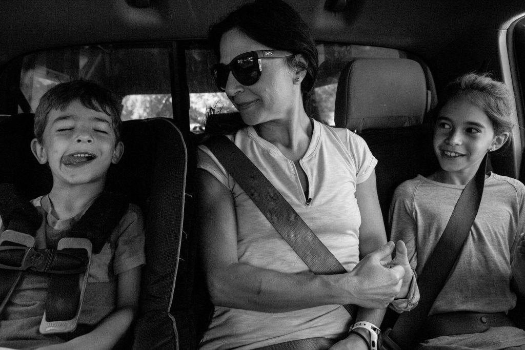 bw of mom in the middle of the back seat playing thumb way with her daughter as her son in a car seat next to her sticks out his tongue.
