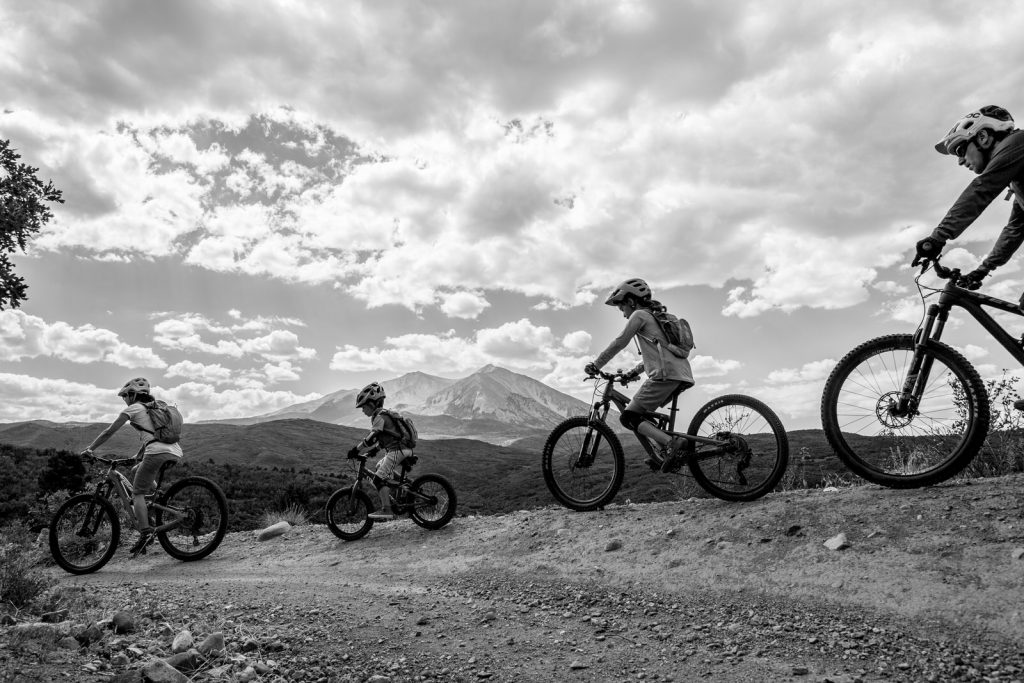 BW of family of four riding mountain bikes with mt sopris in the background
