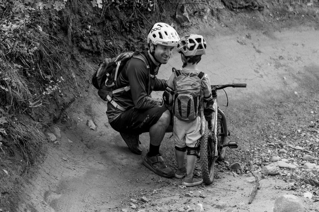 BW of dad squatting down on the trail talking to his mountain biking son