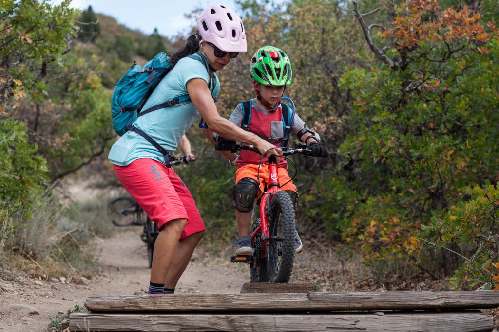 mom in pink yeti bike shorts holds her son's handle bars and holds him steady as he goes over a ramp