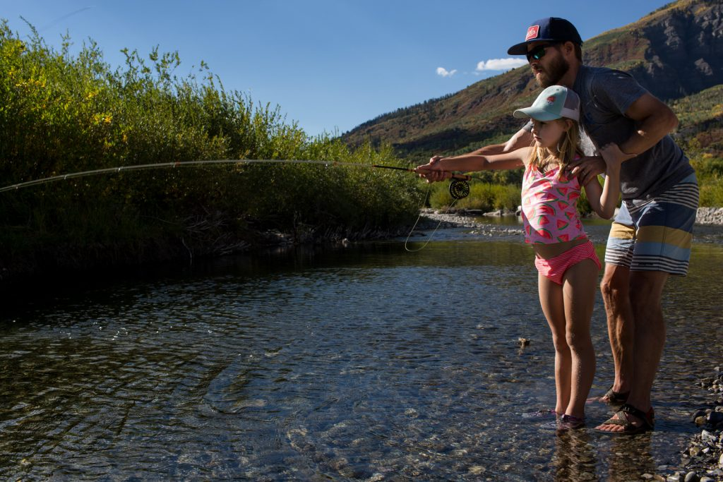 girl and father fly fishing in bathing suits in Aspen during a colorado photography vacation session