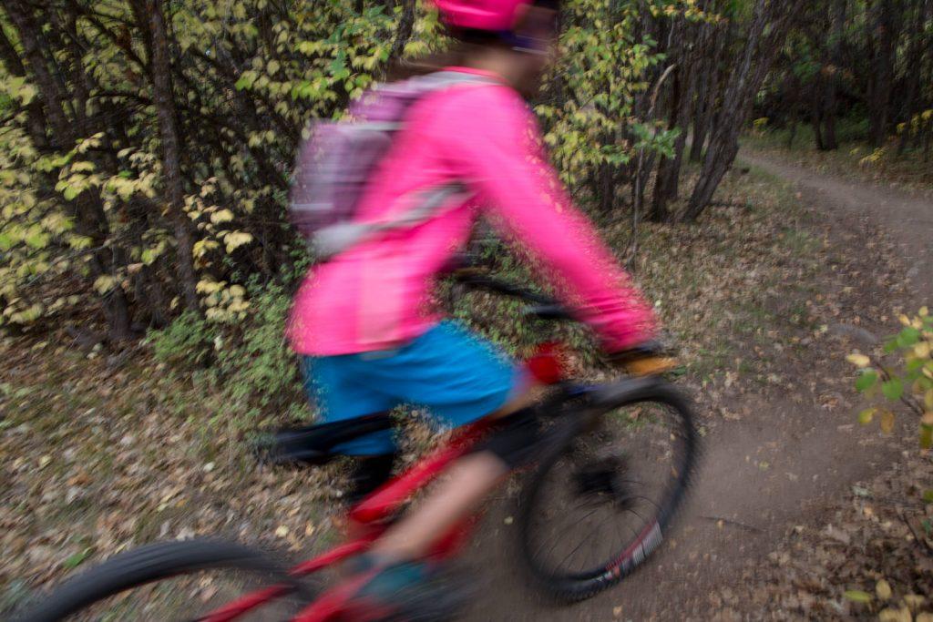 panning image of girl in pink riding mountain bike downhill