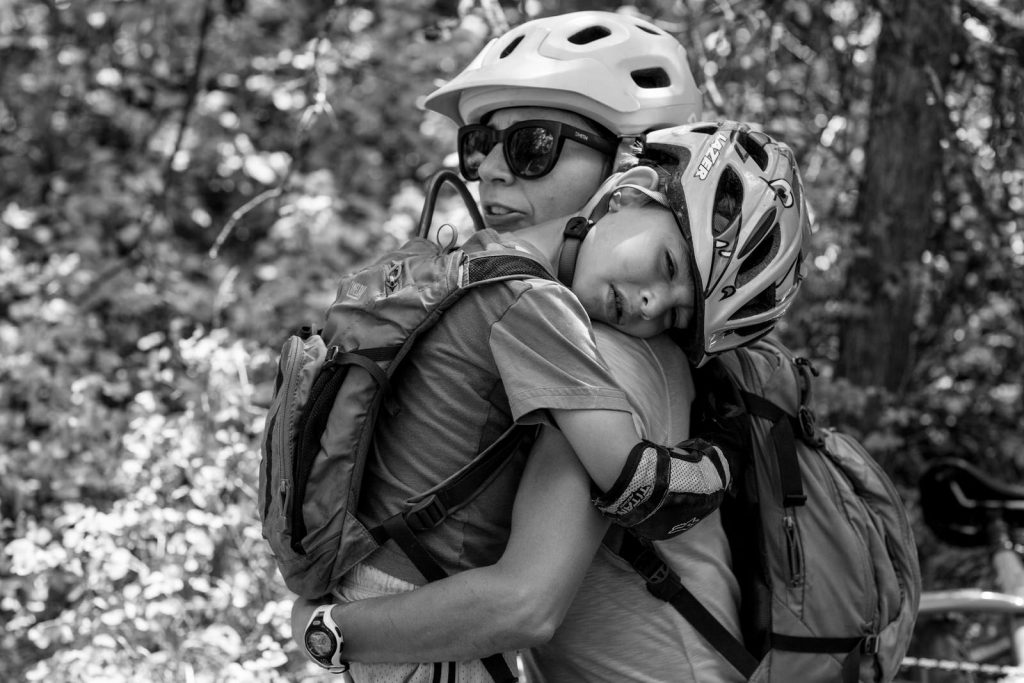 BW of a young boy in biking attire and a helmet being comforted and hugged by his mom