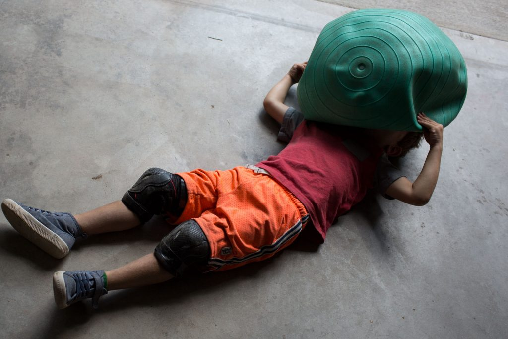 little boy laying on ground with delated exercise ball over his head