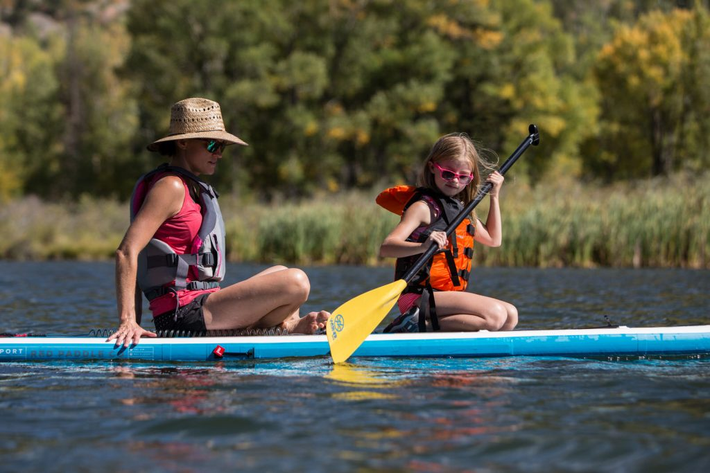 mom and daughter paddling on a SUP on Beaver Lake during a vacation photography session