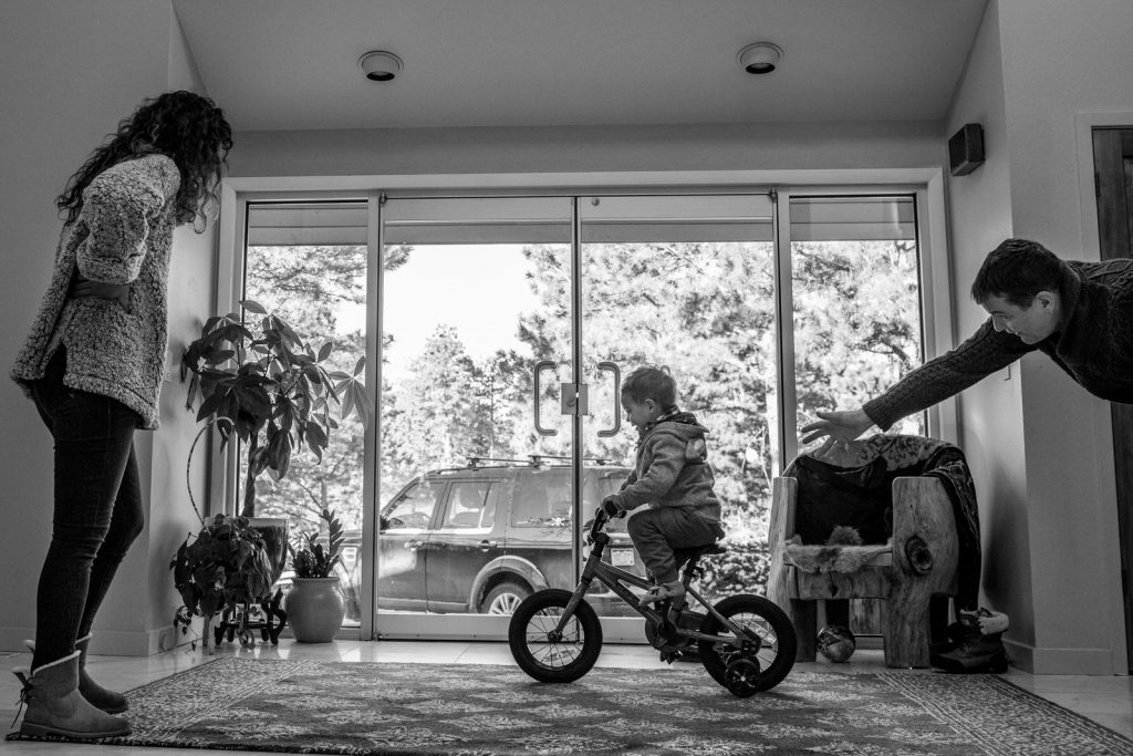little boy learning to ride his small bike in the living room