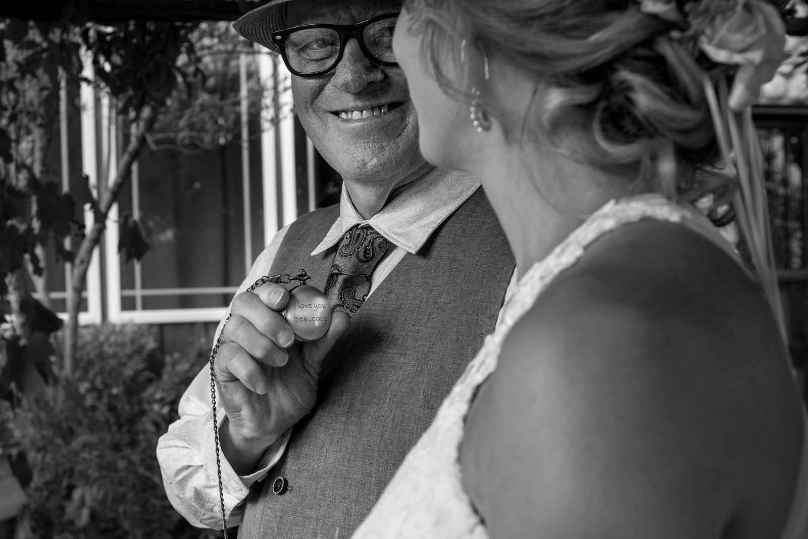 "black and white of the the father of the bride smiling at the bride as he shows her a pocket watch that is engraved with ""I love you beaucoup"""