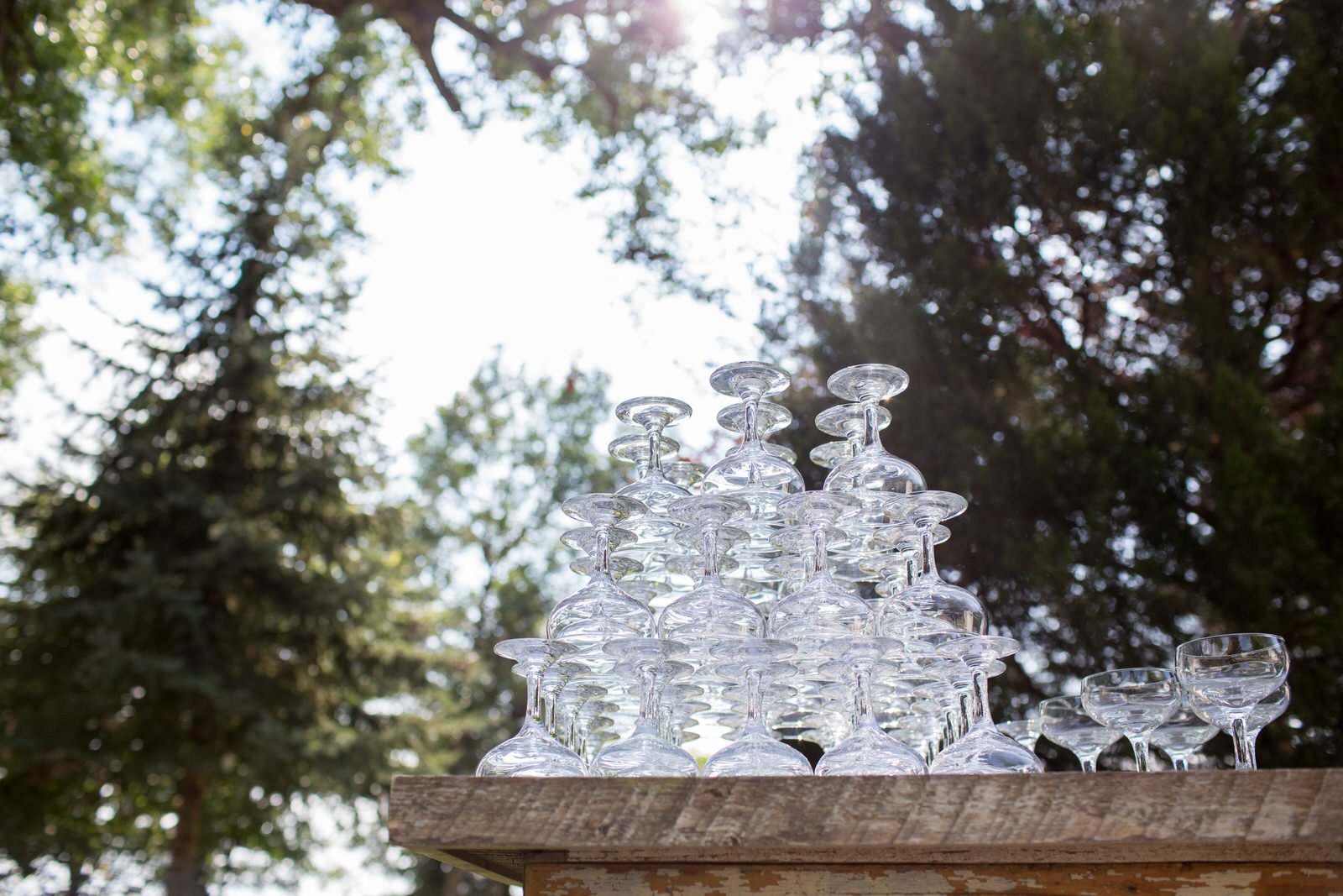 champagne classes stacked in a pyramid and backlit by the sun at milston well farm wedding