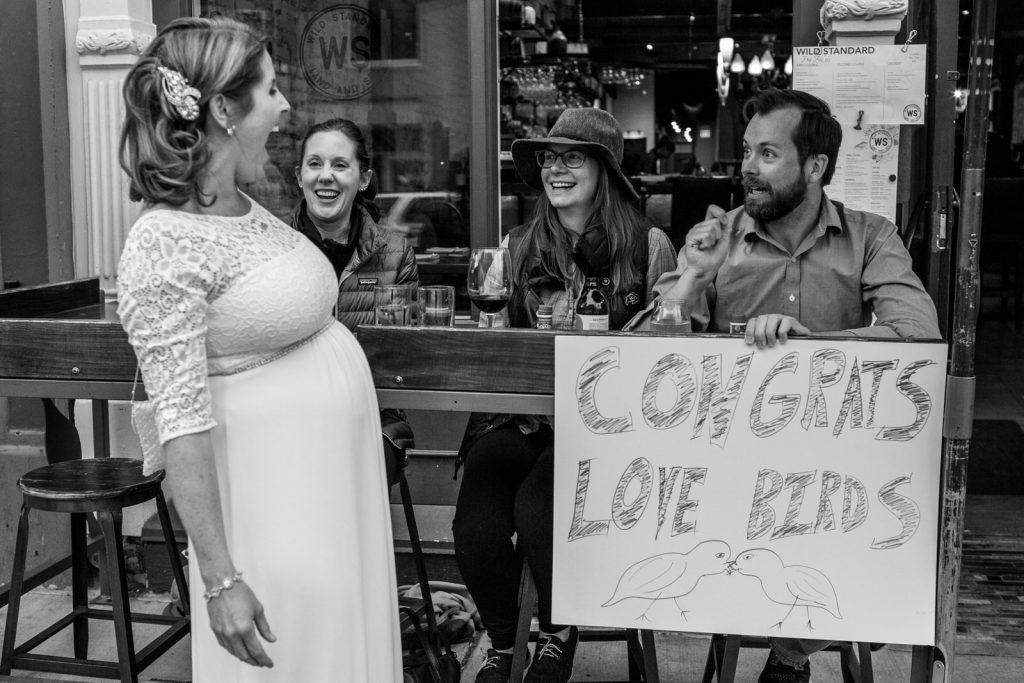 pregnant bride laughs as she reads a sidewalk sign made by friends in boulder colorado