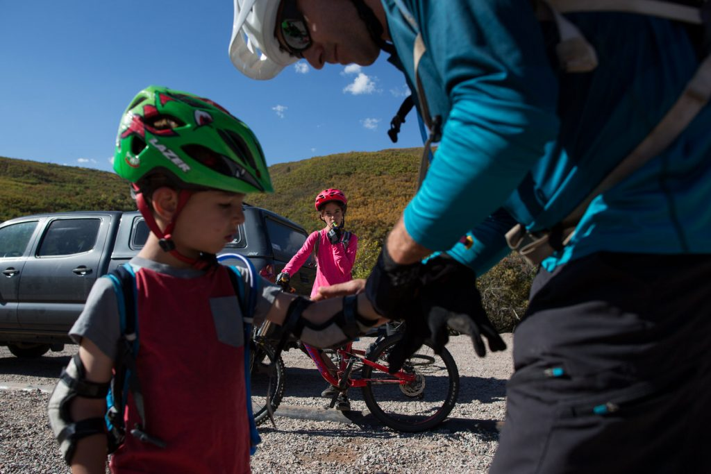 dad adjusts young boys mountain bike gloves as his sister takes a sip from her hydration pack while mountain biking in aspen