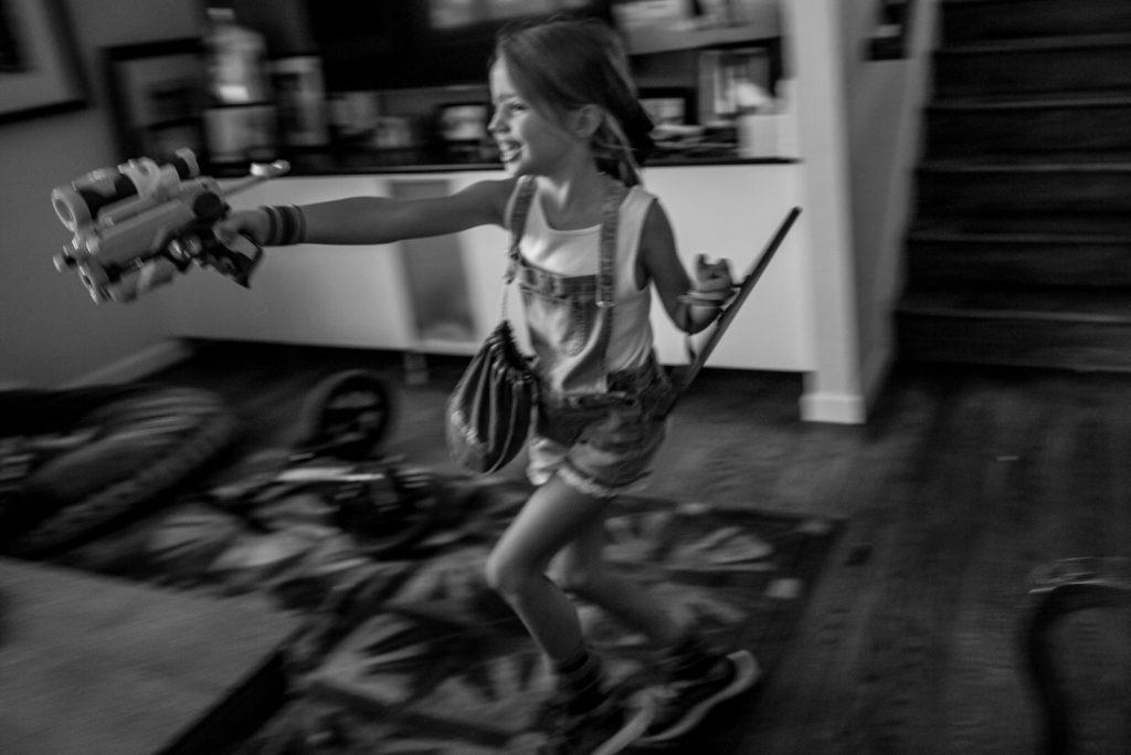 little girl having indoor nerf fun fight in living room