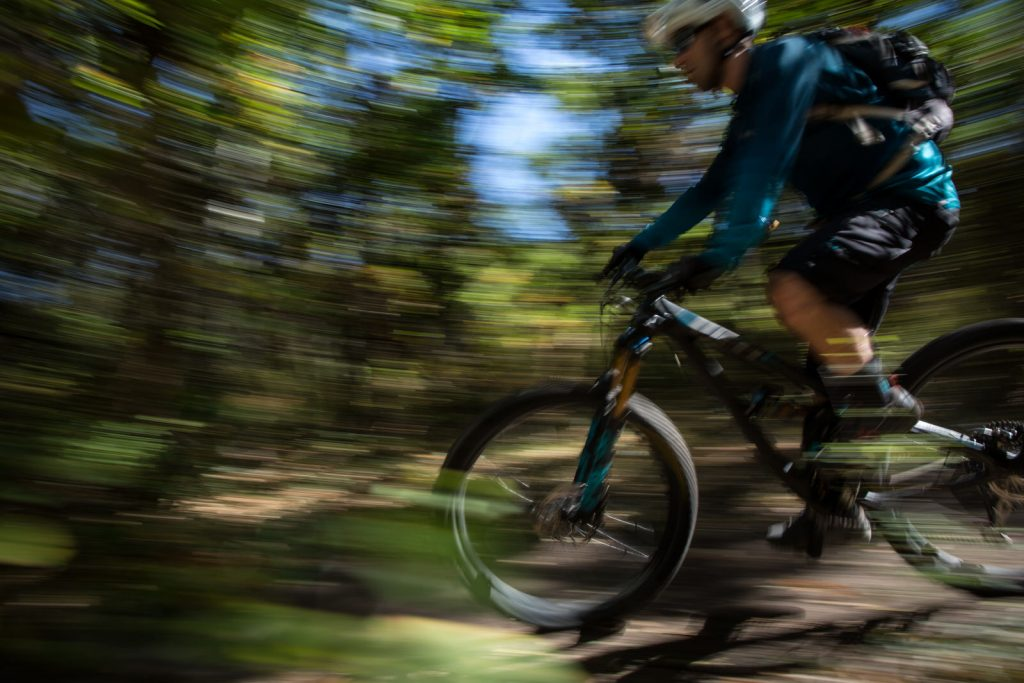 motion blur of a guy mountain biking on a yeti in the green leafed trees in rocky mountains