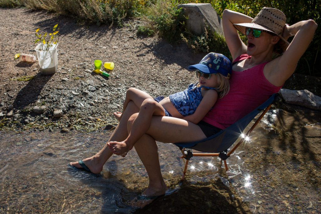 mom sitting in lawn chair in a creek with child on her lap