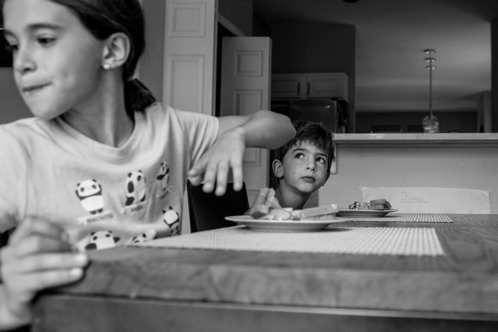 BW of siblings at the table eating and the little brother looking mischievously up at the ceiling