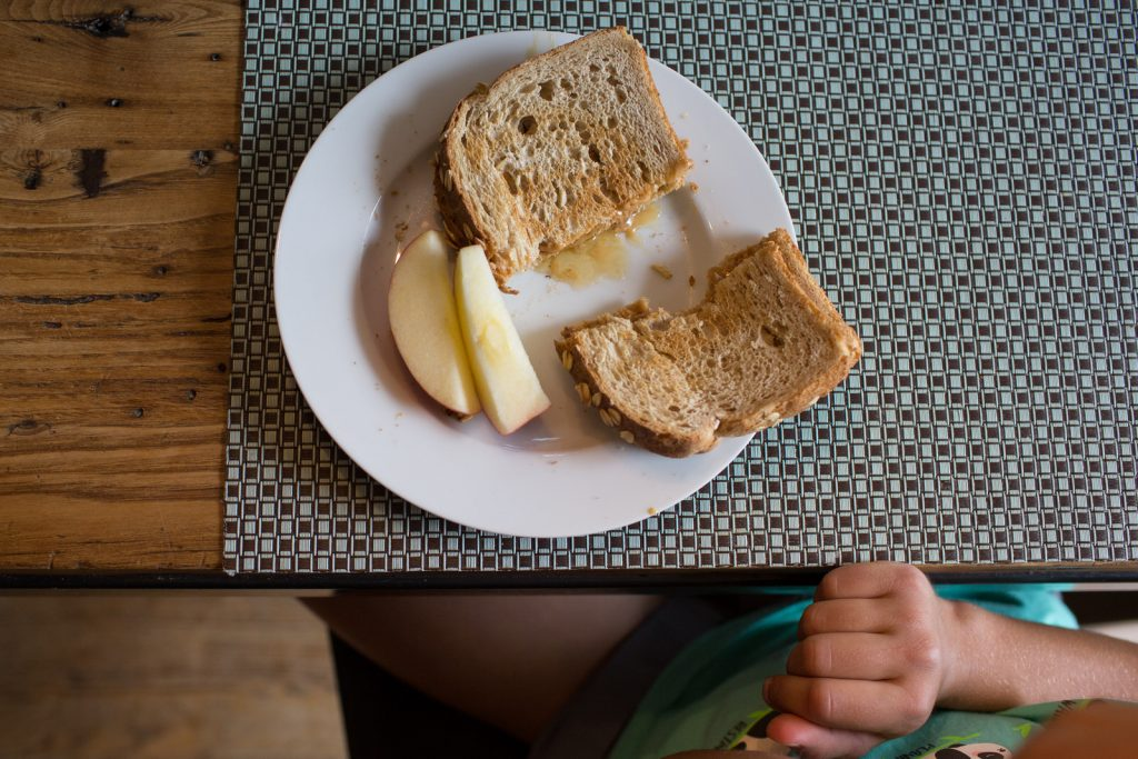 overhead shot of a peanut butter sandwich and apple slices with a little hand