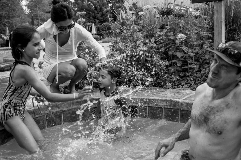 BW of family in a hot tub splashing each other in aspen, co