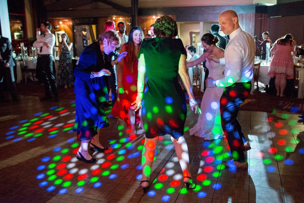 family members dancing during reception at colorado wedding with red green and blue disco lights