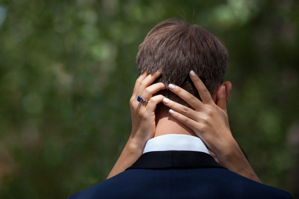 hands of bride on back of grooms head at colorado outdoor wedding by casie zalud