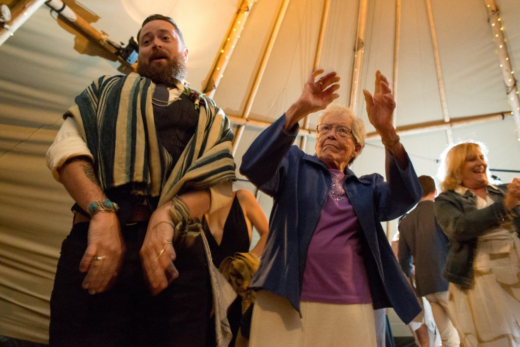 old lady dancing with arms in air at colorado wedding reception