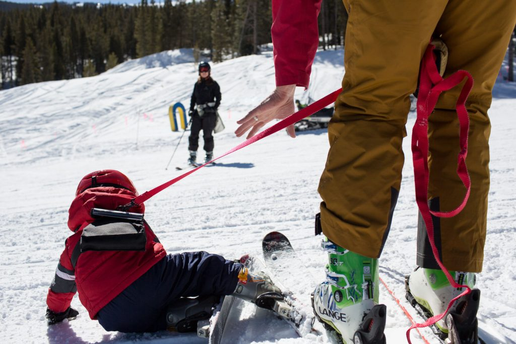 dad helping little kid ski