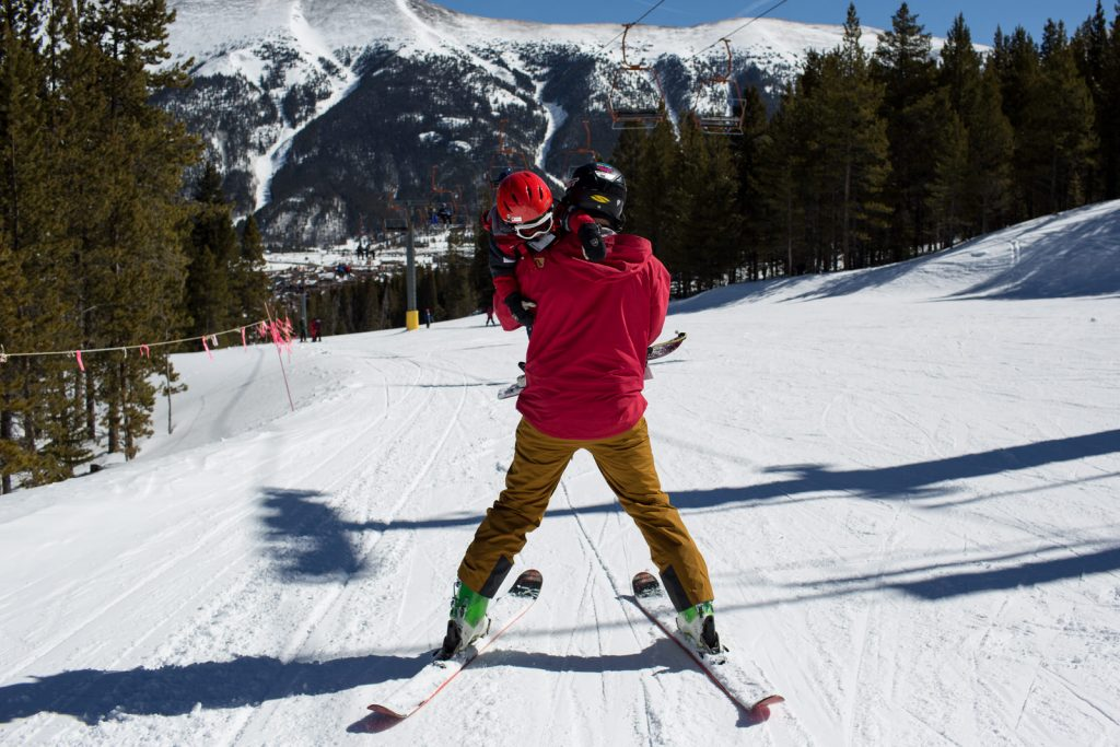 dad skiing down hill at copper mountain, carrying tired boy. All wearing red