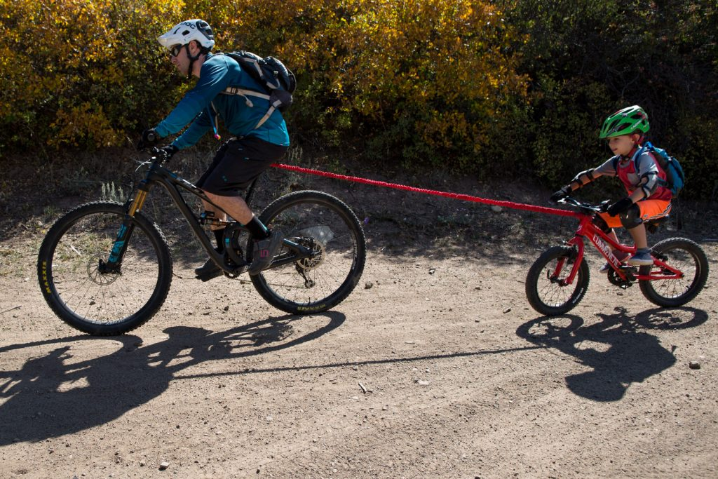 dad pulling small boy on mountain bike in the fall during a aspen family vacation photography session