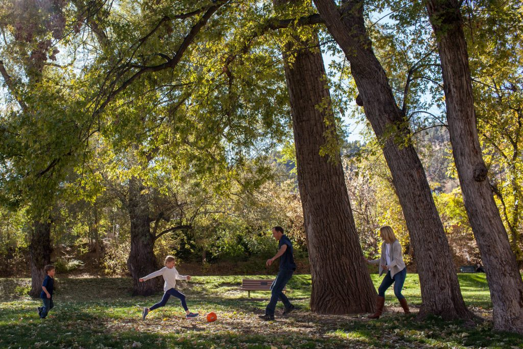 little girl kicking ball to dad and mom during a boulder family photo session