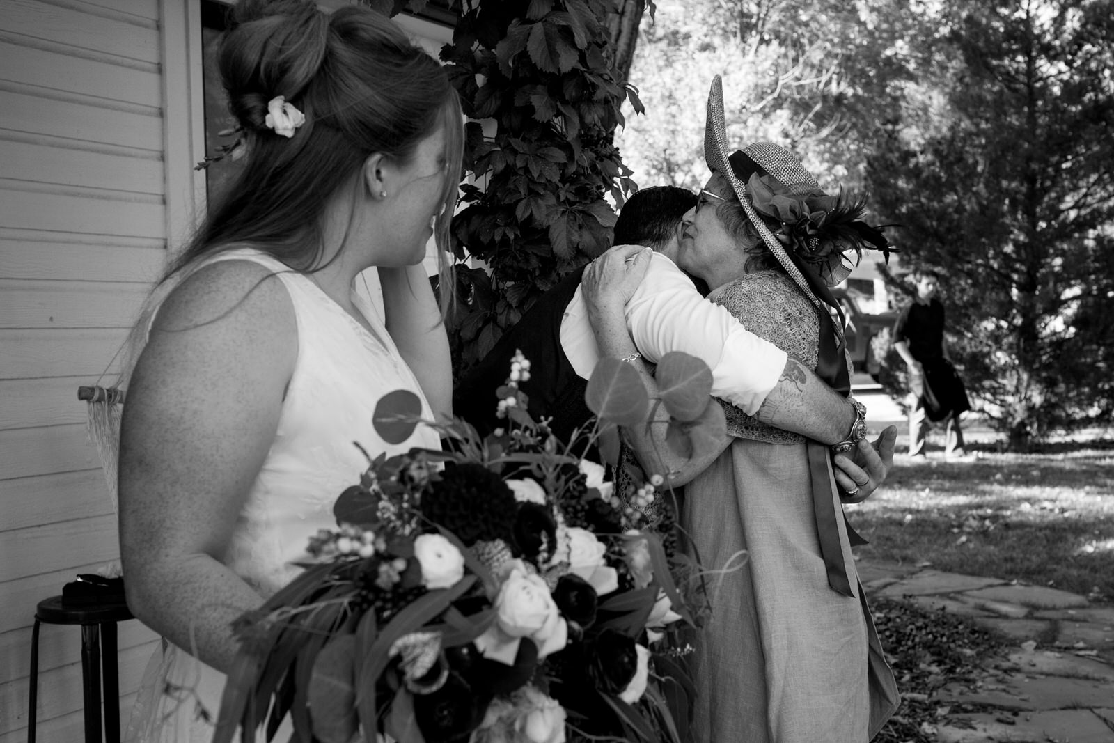 black and white of a groom hugging his mom as his new wife looks on