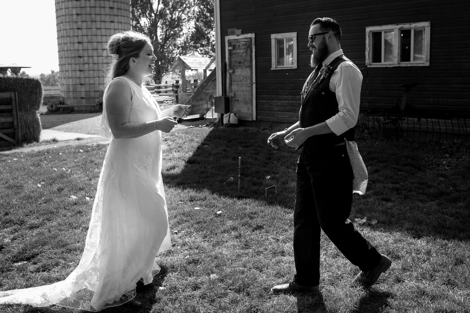 black and white of bride and groom walking towards each other at milston well farm with big grins for their first look at each other