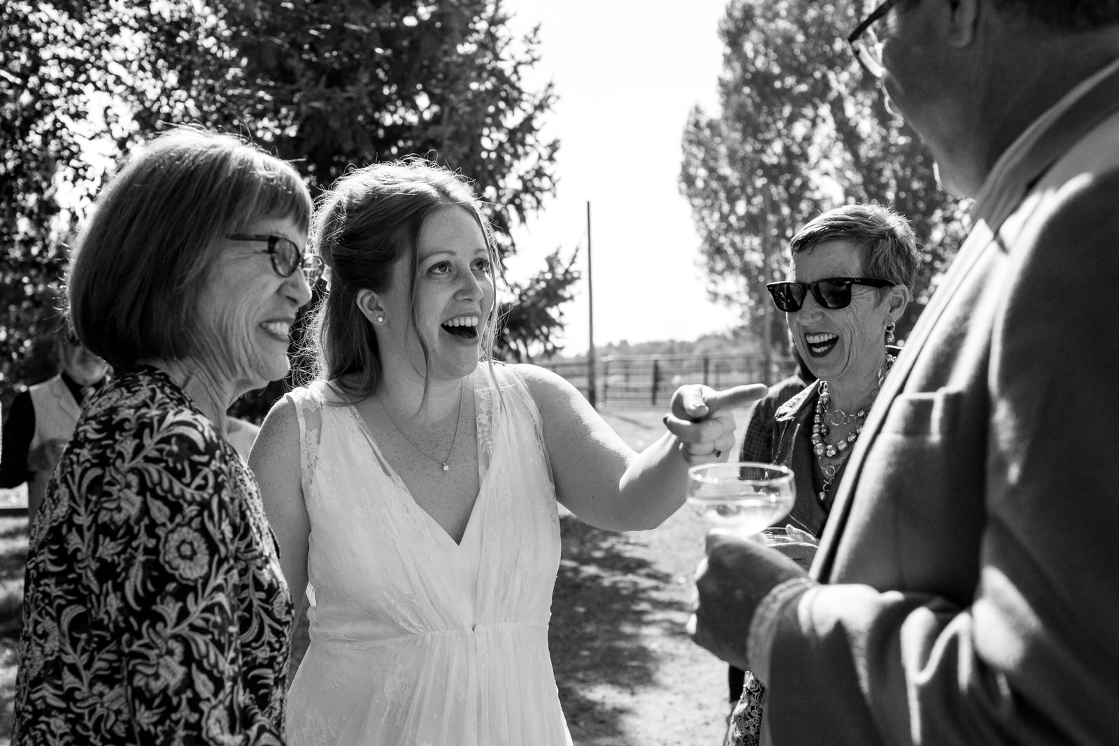 black and white of a bride and her mom laughing with guests at her outdoor farm wedding