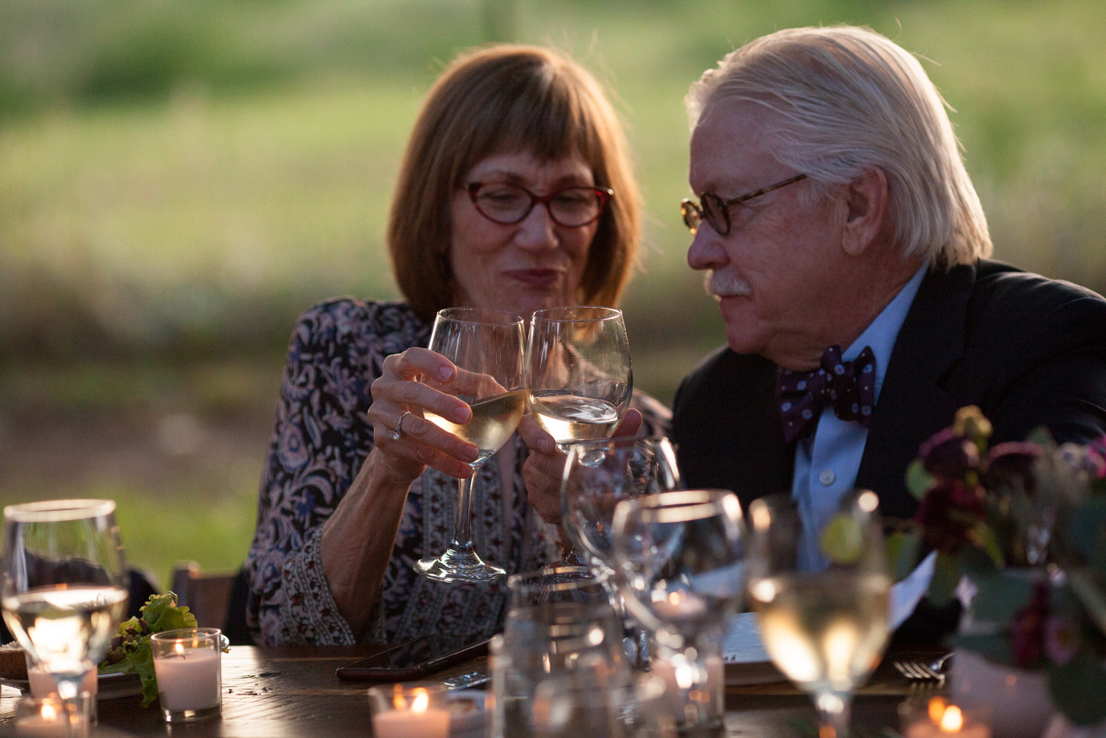 color photo at golden hour of an older couple toasting each other with white wine