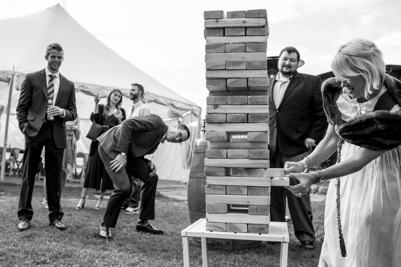 black and white of a family at an outdoor wedding playing giant sized jenga while laughing and cajoling each other