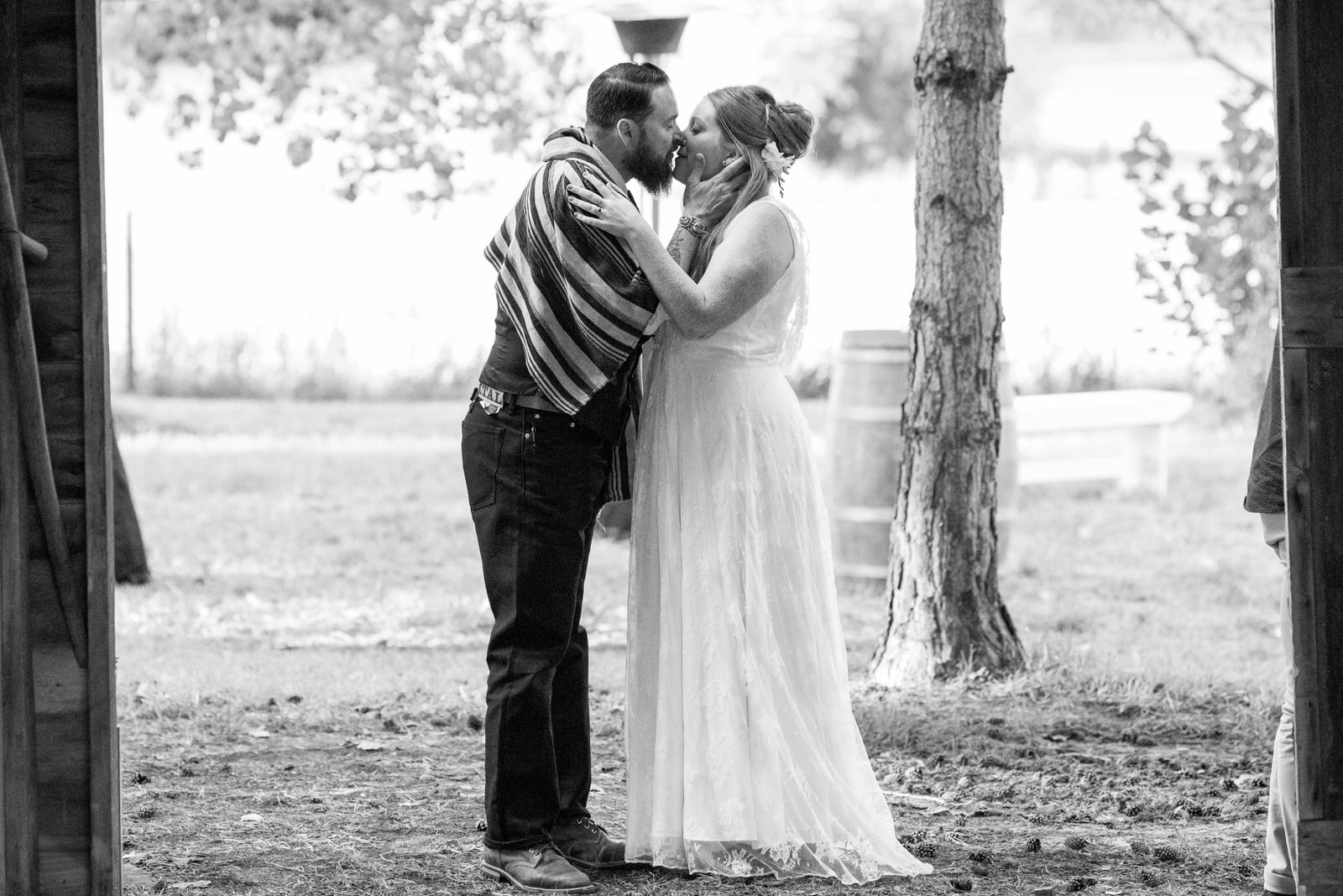 black and while of a groom and bride kissing outside of a barn door at milston well farm