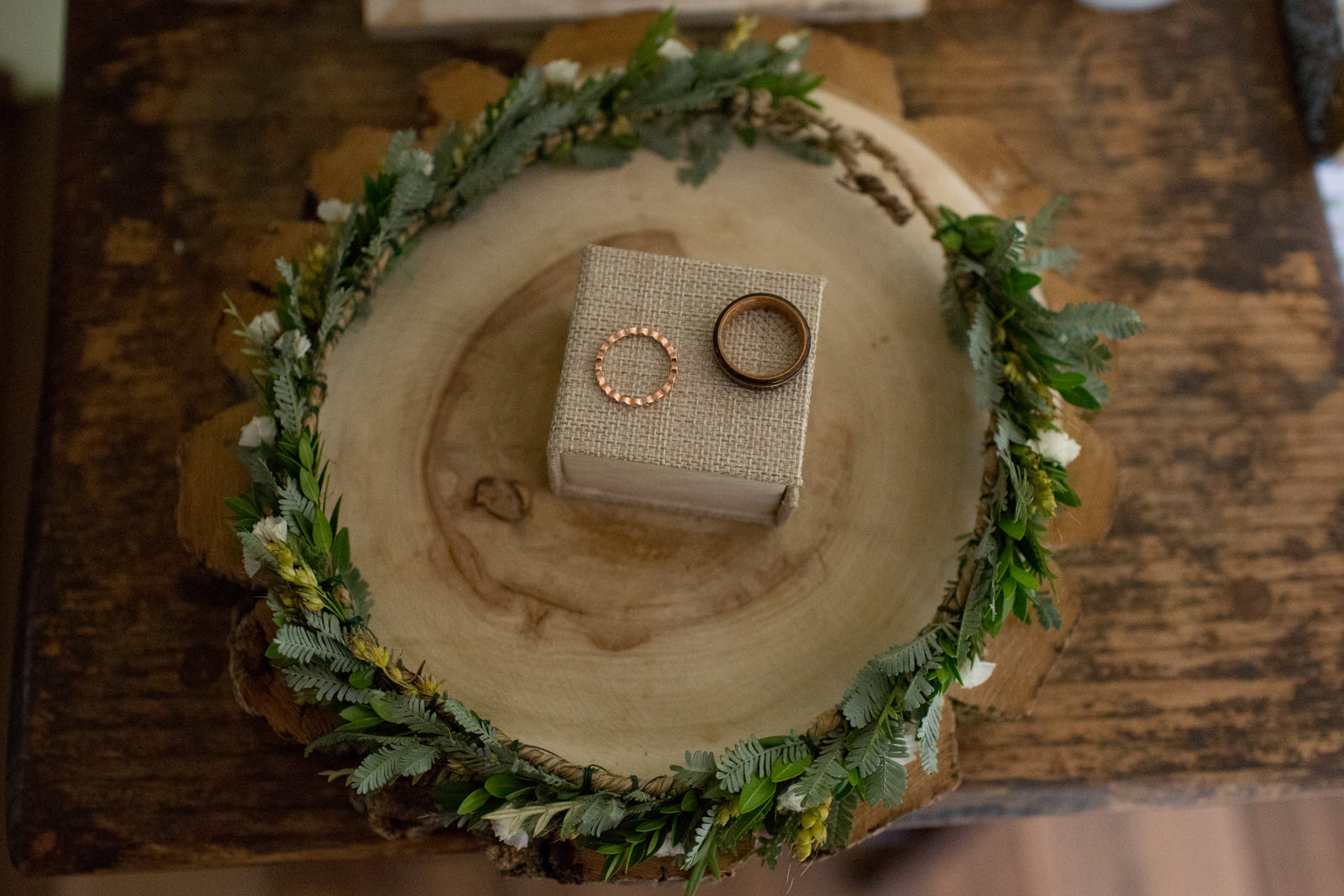 a copper female wedding band and a wooden male wedding band on a burlap box an a stump of wood with a floral crown surrounding it