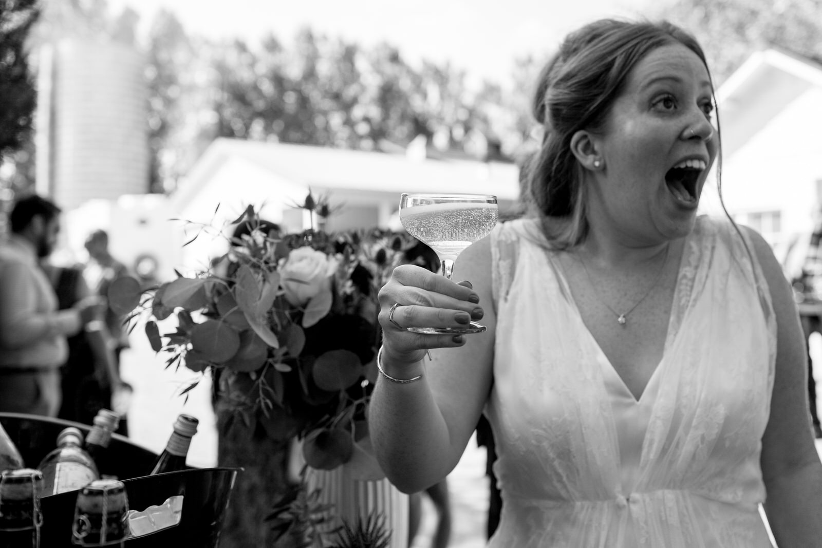black and while of bride holding a glass of champagne with joy and excitement on her face at her milston well farm wedding