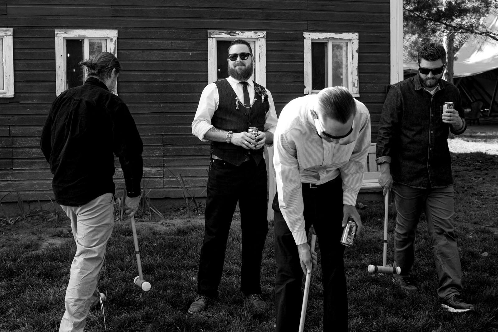 black and white of groom smiling off to the distance as he is surrounded by his pals as they are playing croquet