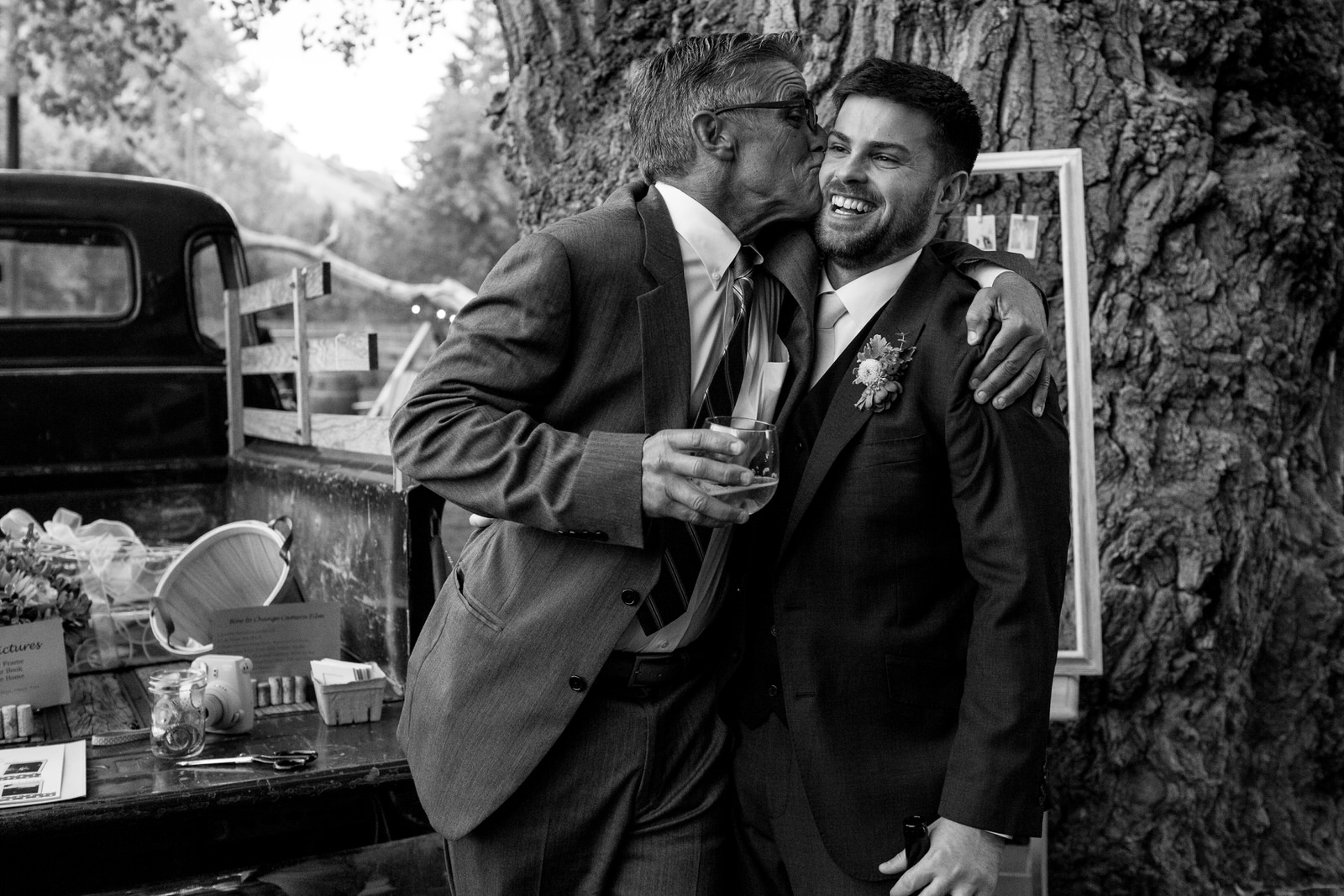 black and white of father of the bride passionately kissing the groom on the check as the groom laughs