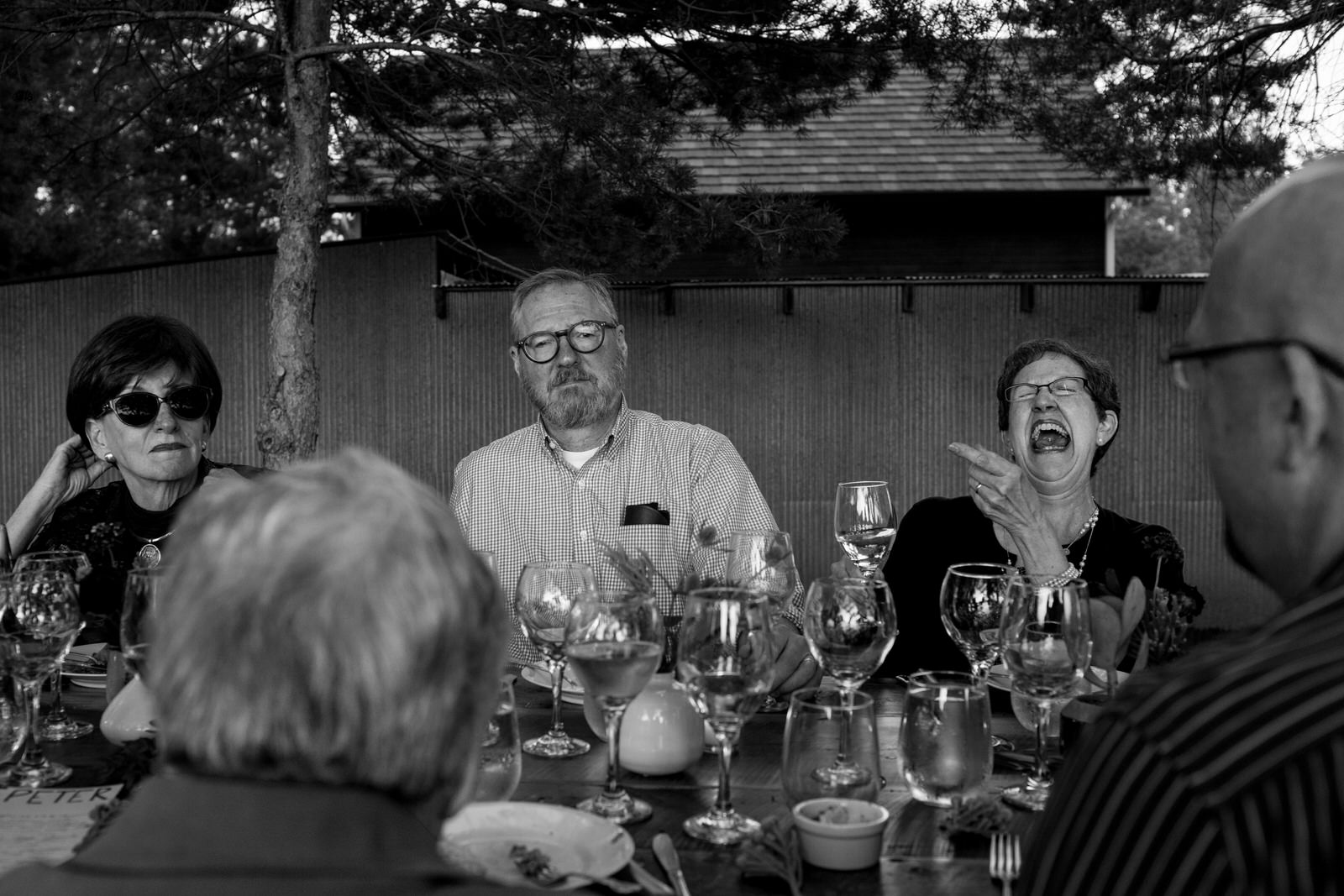 black and white of guests at dinner, one woman laughing hysterically while pointing at the guy sitting next to her who is frowning