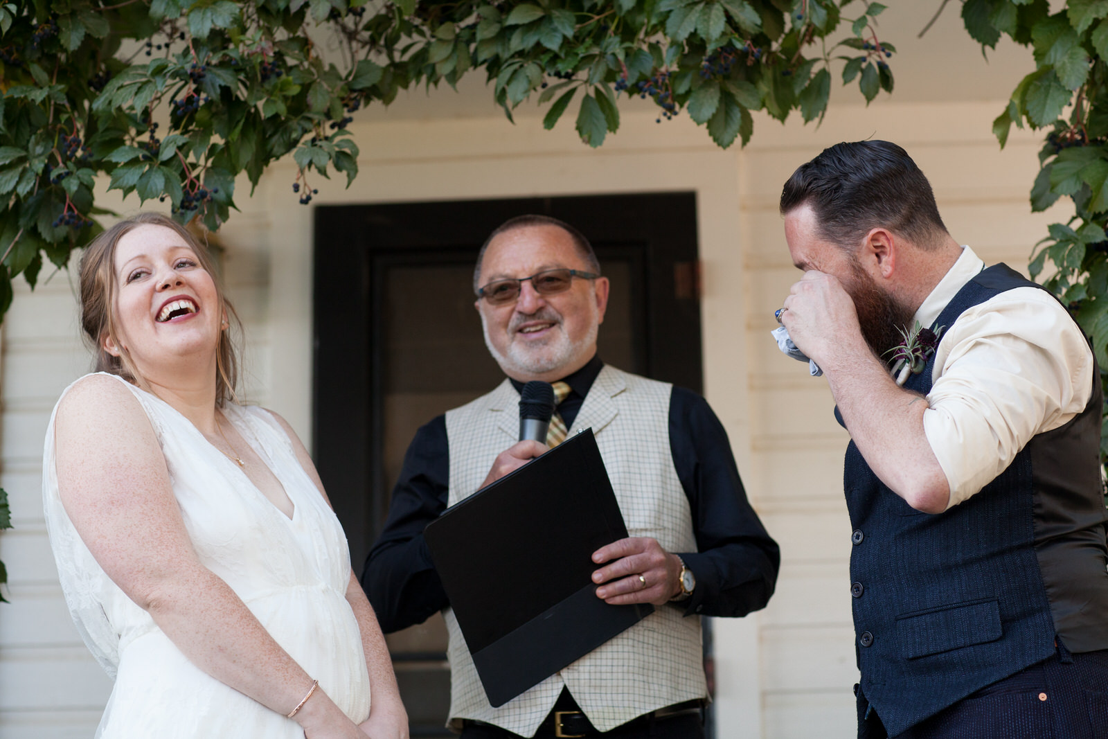 bride and groom at a ceremony on the porch of a white cottage with greenery framing the couple at milston well farm