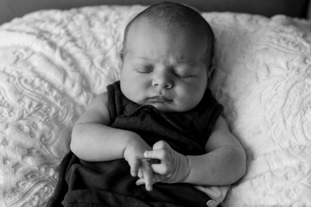 sleeping baby with scrunched face and hands clasps together