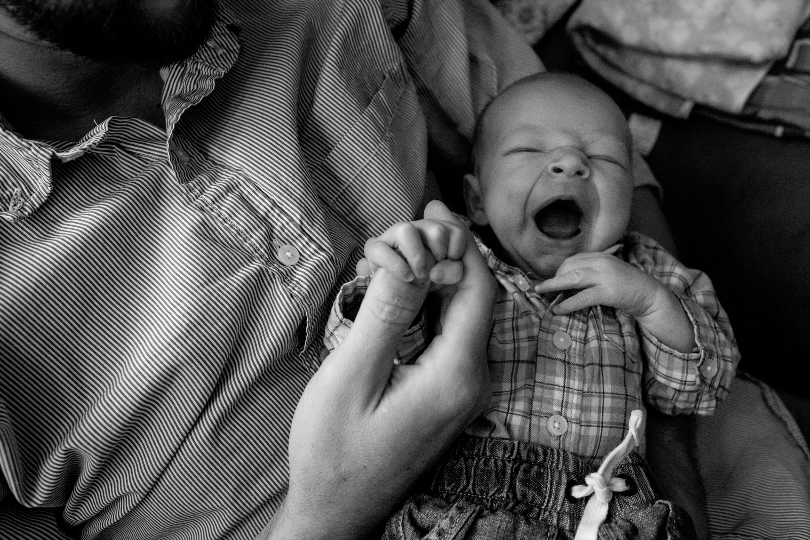 newborn baby smiling gripping dad's pointer finger.