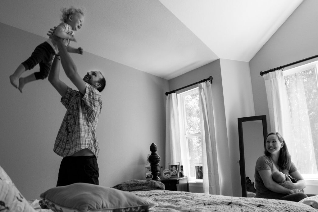 mom feeding newborn while dad throws toddler in air with laughter and glee during a newborn photography session with casie zalud