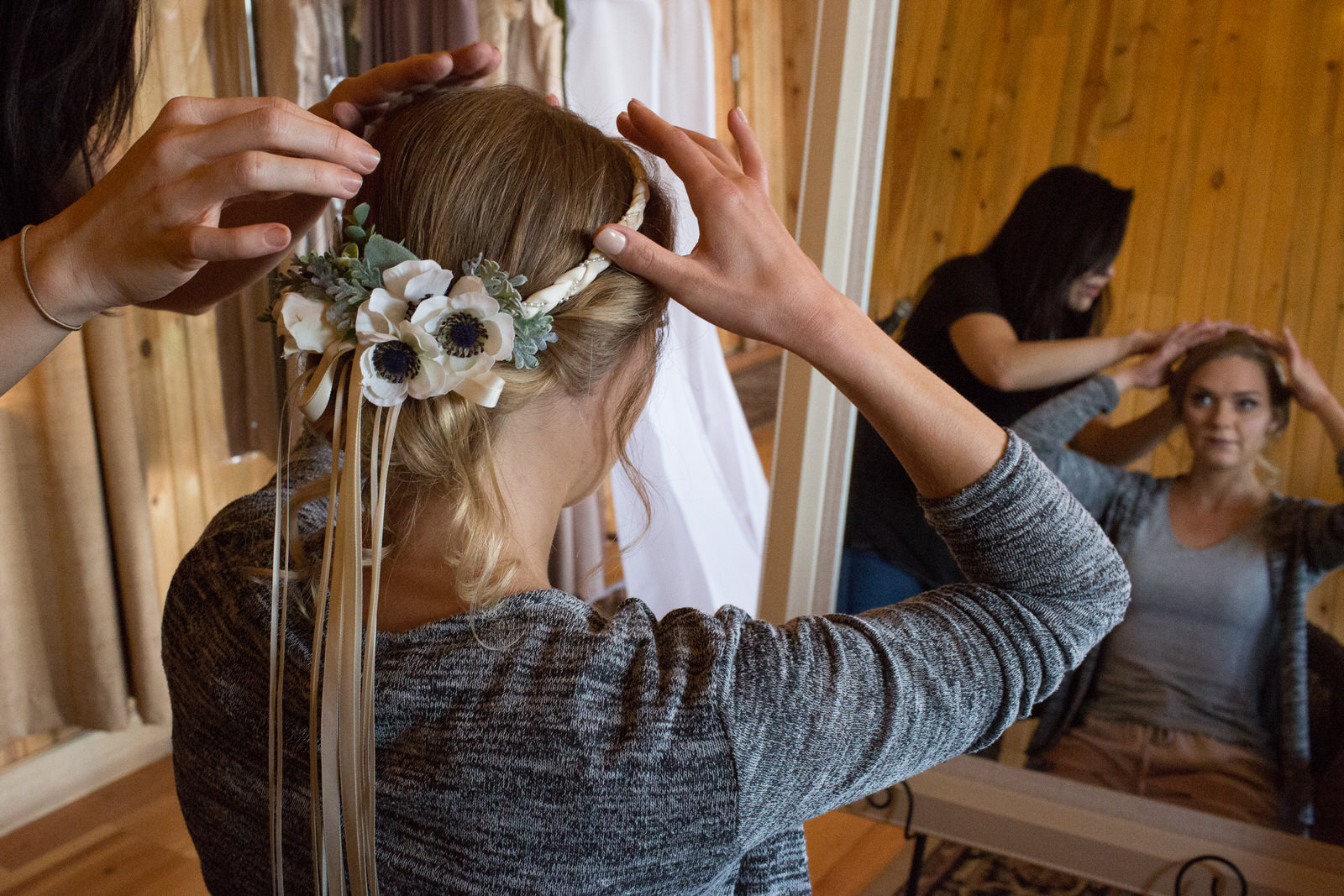 flower crown being placed on a bride as she looks at herself in the mirror and the stylist makes it perfect