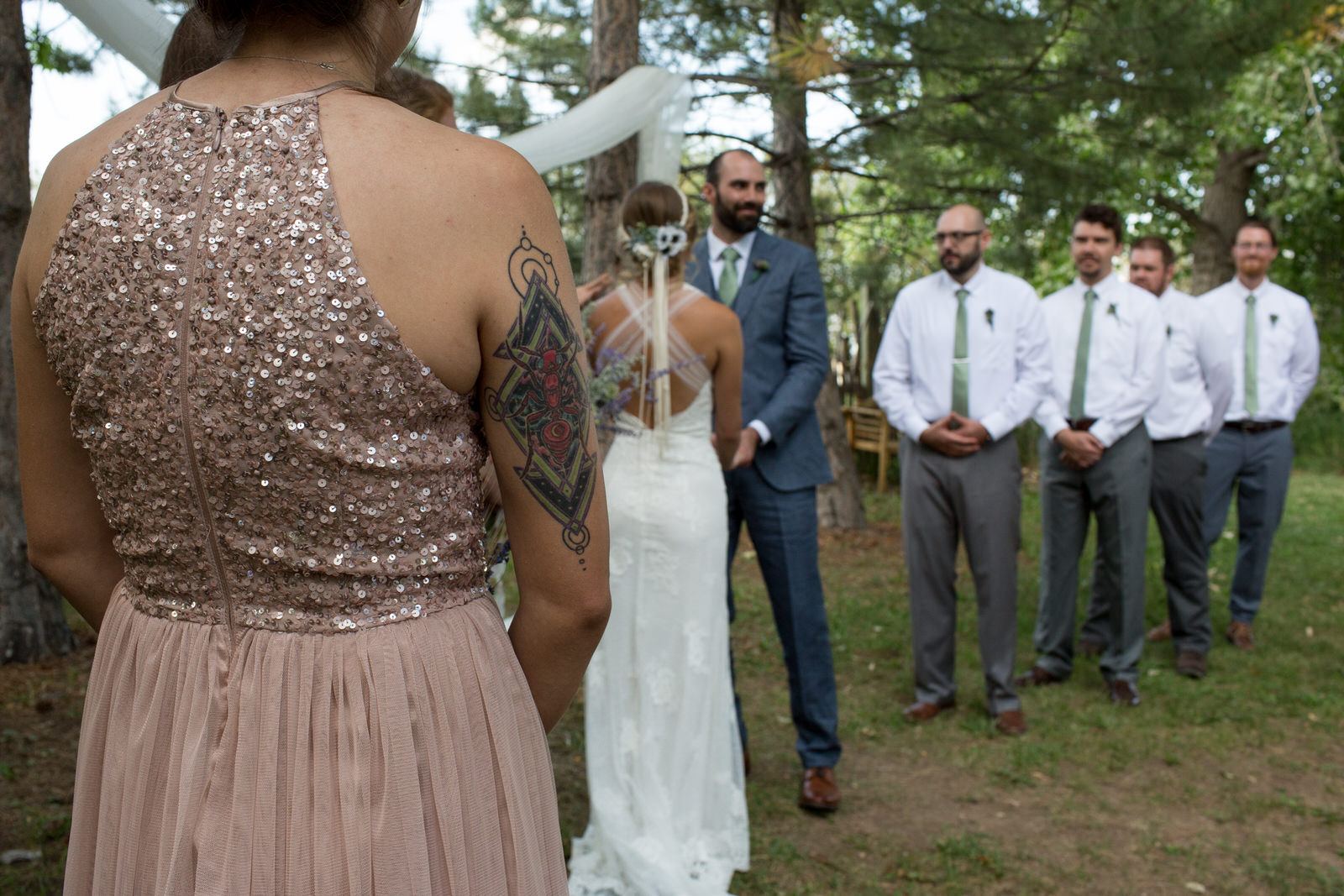 diamond shaped tattoo on the back of the arm of one bride's maid who was wearing a rose sequin dress at lone hawk farm wedding