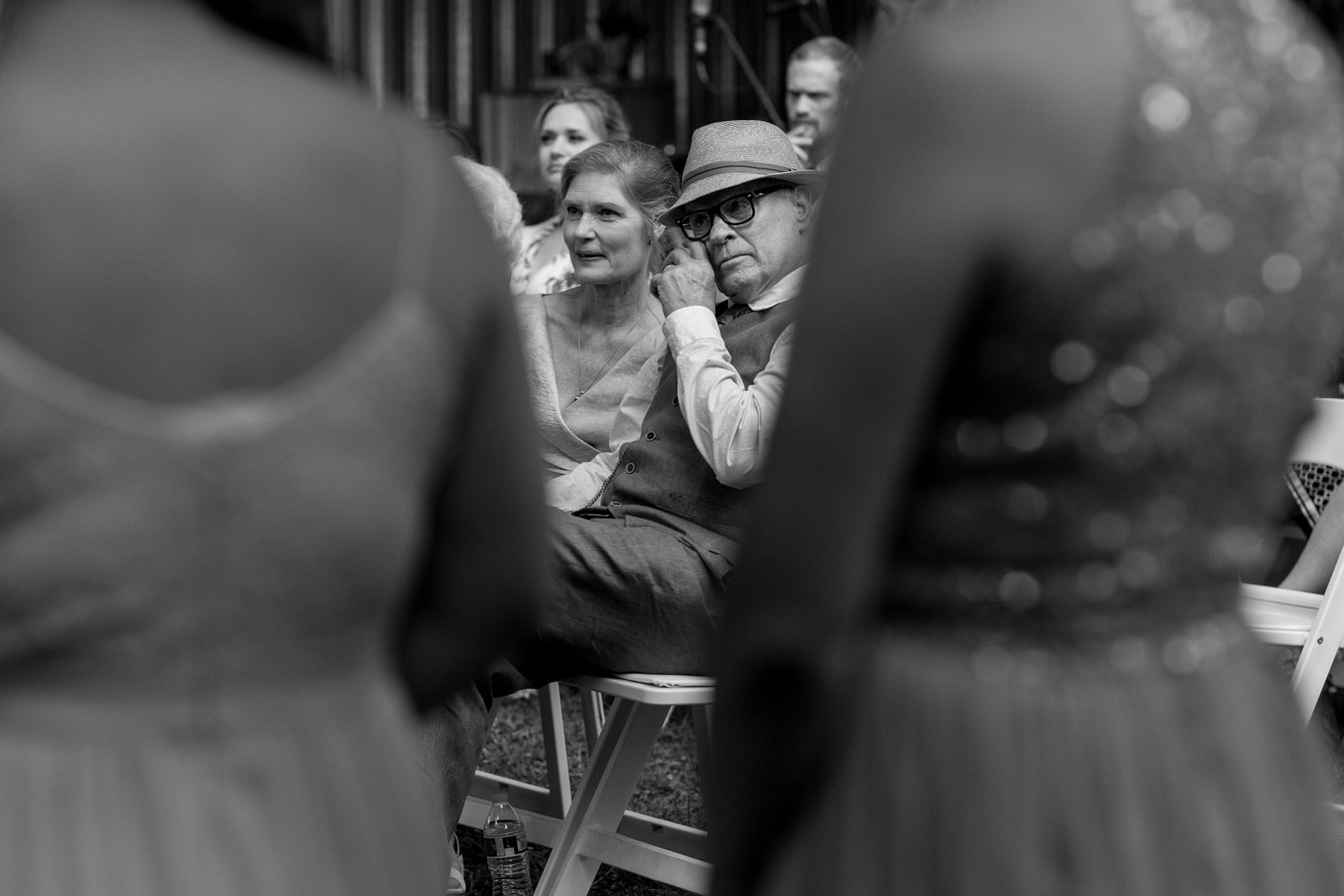 black and white of a father of the bride wiping a tear from his eye during the ceremony, framed by the torsos of two bridesmaids