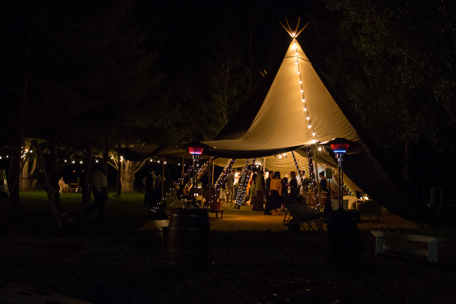 evening shot of a tee pee at milston well farm wedding with lights and heaters at an outdoor Colorado farm wedding