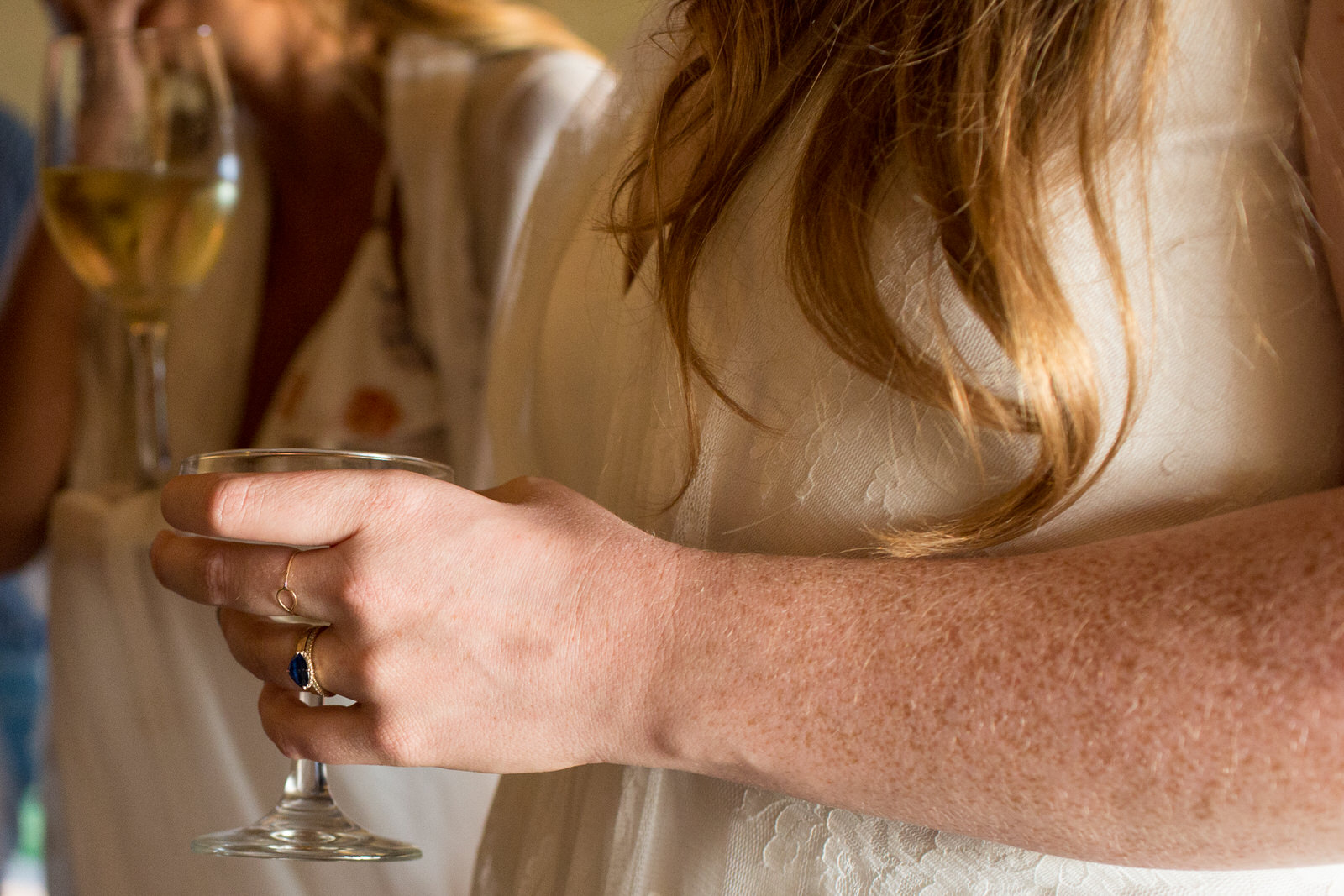 bride's hand holding a champagne glass and showing off her sapphire wedding ring